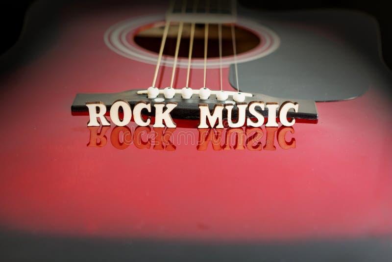 Musica rock di parole con le lettere di legno, su superficie riflettente di una chitarra acustica Prospettiva del ponte delle chi fotografie stock