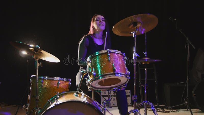 Musica rock teenager - il batterista attraente della percussione della ragazza esegue la musica riparte fotografia stock
