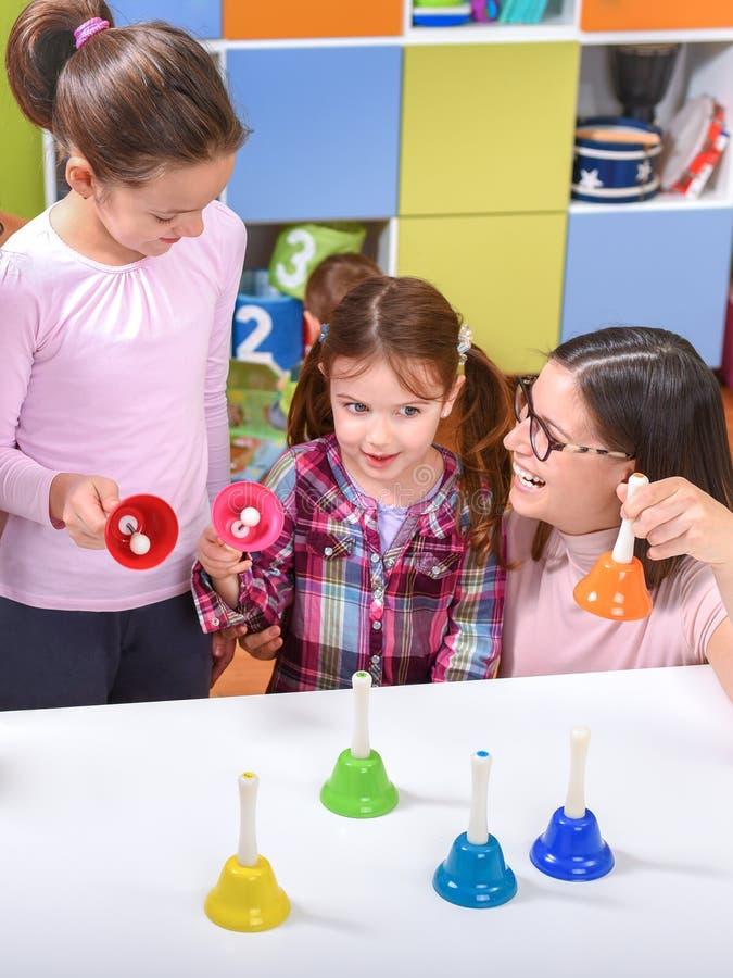Musica sorridente Belhi della tenuta di With Cute Kids dell'insegnante fotografia stock