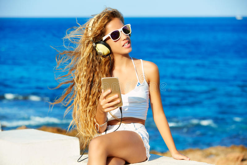Musica teenager delle cuffie della ragazza del bambino biondo sulla spiaggia fotografia stock