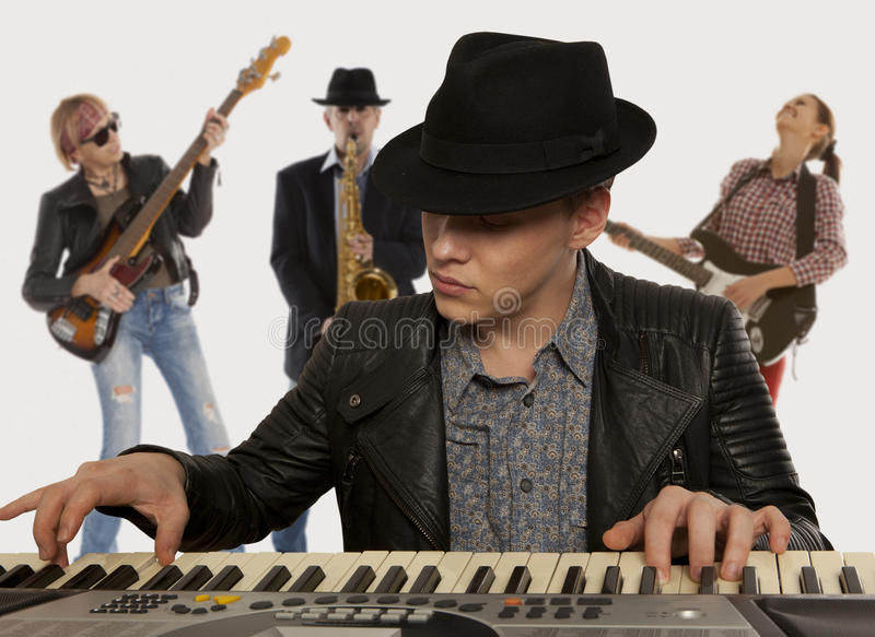 Musical band. Man in the hat playing on a synthesizer stock photo