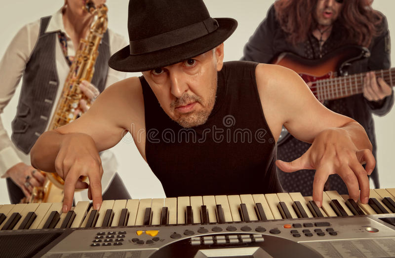 Musical band. Man in the hat playing on a synthesizer royalty free stock photo