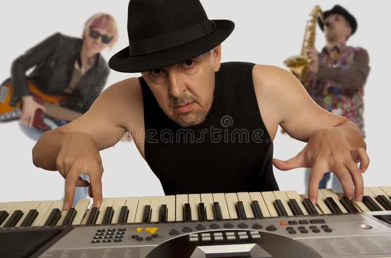 Musical band. Man in the hat playing on a synthesizer royalty free stock photos