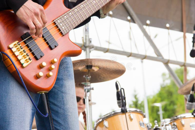 Musical band perfom on an open air festival. Bass guitarist man playing close, drums blurry royalty free stock image