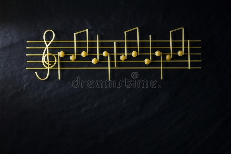 Musical Christmas sheet music paste isolated on a black textural background. The concept of cooking as art stock image