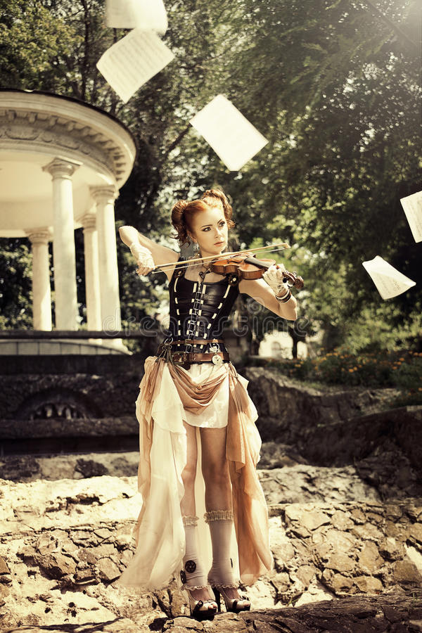 Musical concept. Beautiful young woman in rock style clothes playing on violin outdoors. royalty free stock photography