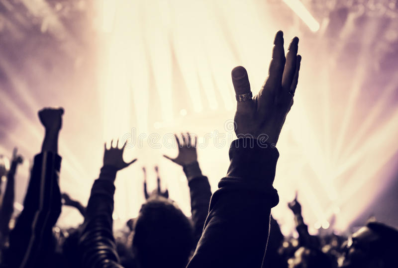 Musical concert. Grunge style photo of silhouette of people hands raised up on musical concert, enjoying music, dance club, active night life concept royalty free stock image