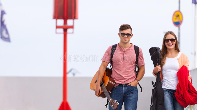 Musical couple walking with instruments. Love romance music sound relationship dating concept. Musical couple walking with instruments. Girl and boy taking walk royalty free stock images
