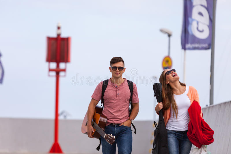 Musical couple walking with instruments. Love romance music sound relationship dating concept. Musical couple walking with instruments. Girl and boy taking walk stock image