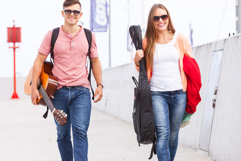 Musical couple walking with instruments. Love romance music sound relationship dating concept. Musical couple walking with instruments. Girl and boy taking walk royalty free stock photography