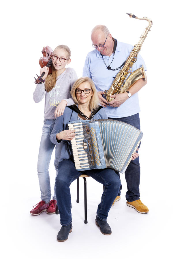 Musical family with saxophone, violin and accordion in studio stock image