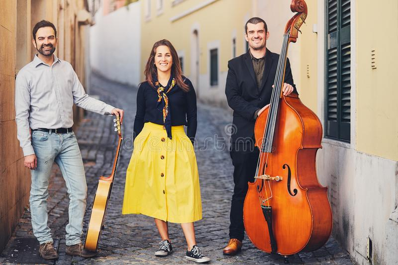 A musical group of three people on an old European street. The band consists of two men and one girl. Men with a double bass and a. Guitar. Unconventional stock photography