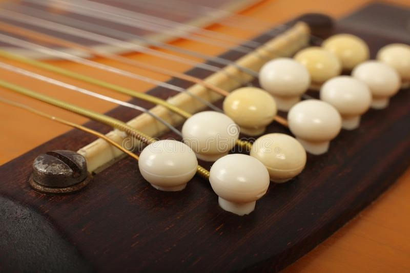 Musical instrument - bridge pins twelve-string acoustic guitar royalty free stock images