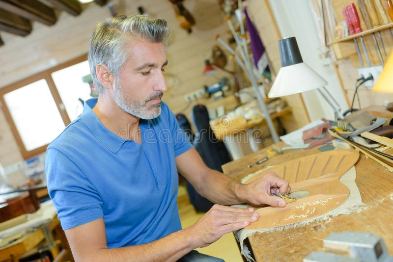 Musical instrument maker at workbench stock image