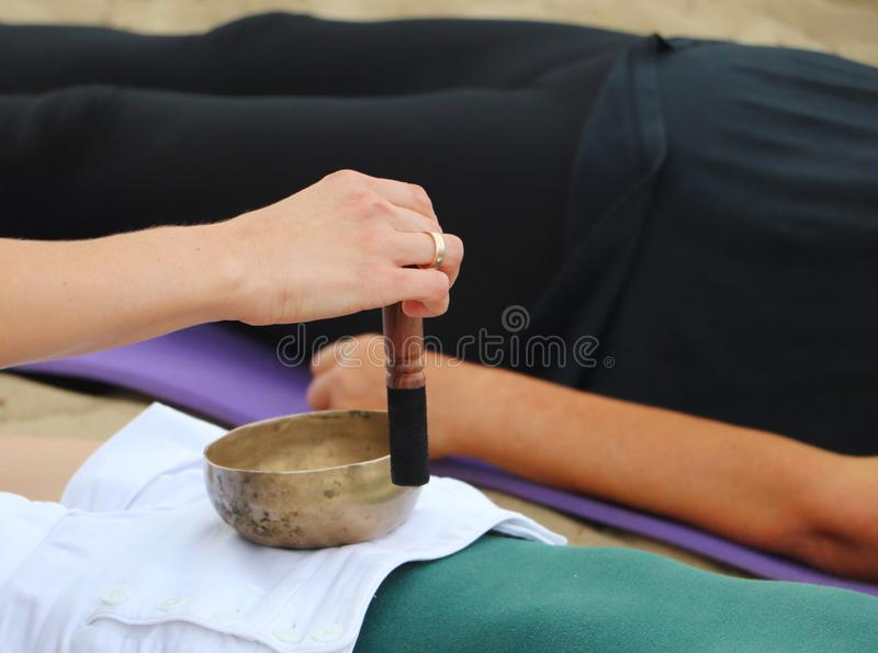 Musical instrument - singing Himalayan bowl. The singing bell holds the girl in his hand. The practice of healing vibrations,. Yoga, meditation stock photo