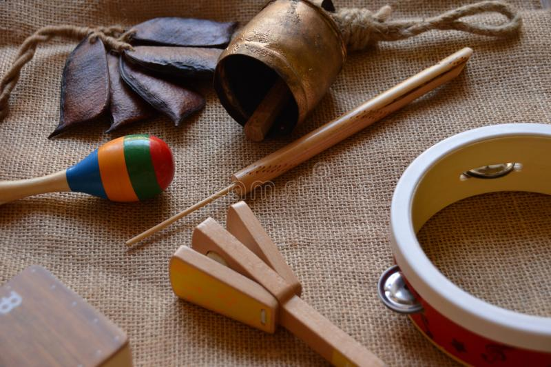 Musical instruments for babies and children. Maraca, cowbell, tambourine, flute, music box, shaker, sea shell, seed rattle and castanet with handle royalty free stock image