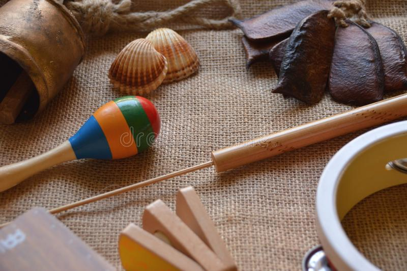 Musical instruments for babies and children. Maraca, cowbell, tambourine, flute, music box, shaker, sea shell, seed rattle and castanet with handle royalty free stock photography