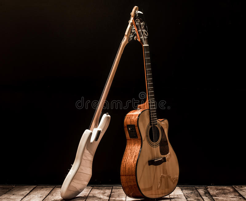 Musical instruments, bass drum barrel acoustic guitar and bass guitar on a black background. The music concept royalty free stock images