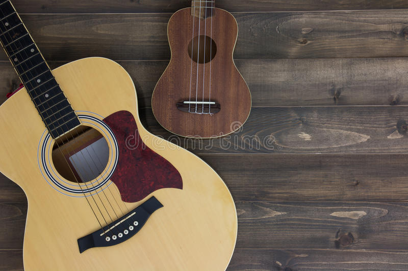 Musical instruments guitar ukulele. On old wooden background with copy space. Vintage effect royalty free stock photo