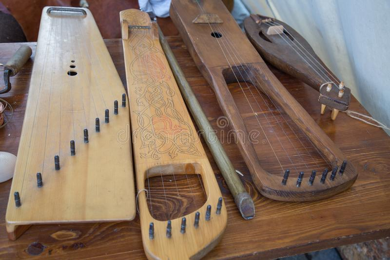 Musical instruments gusli horn on the table of brown boards royalty free stock photography