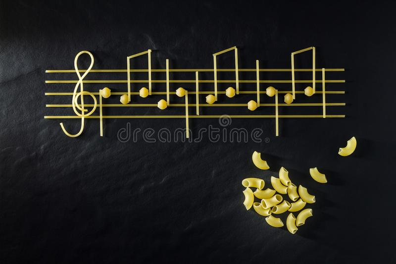 Musical Italian pasta in the form of notes, isolated on a black textural background royalty free stock photo