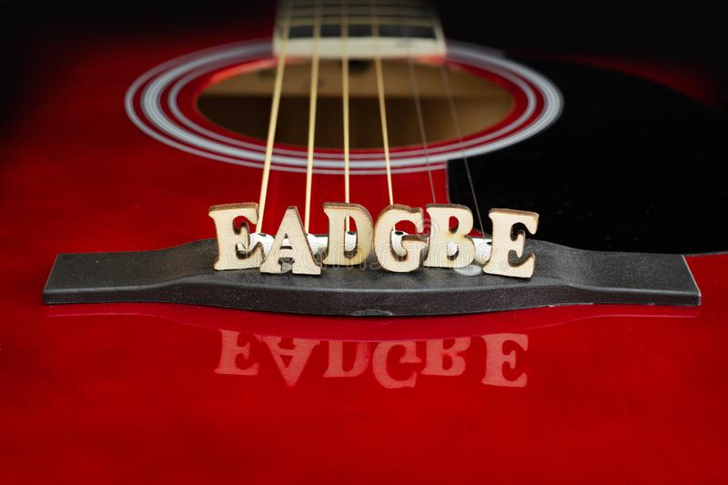 Musical notes EADGBE in corresponding to strings arrangement, with wooden letters, on the bridge of an acoustic guitar. Guitars stock photography