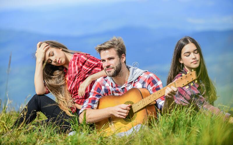Musical pause. Hiking entertainment. Peaceful place. Melody of nature. Hiking tradition. Friends hiking with music. People relaxing on mountain top while royalty free stock image