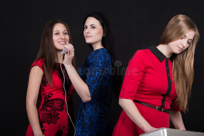 Musical performance. Girls band musical performance. Beautiful smiling female singers with microphone and young musician in red dress with synthesizer on royalty free stock images