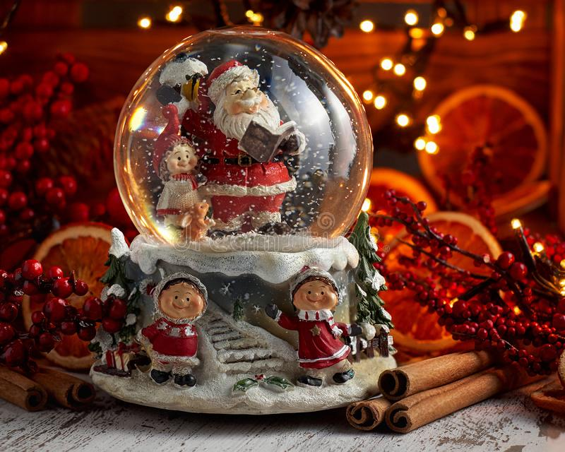 Musical Snow Globe with Santa Claus on bokeh background. Musical Snow Globe with Santa Claus. Christmas or New Year gift on bokeh background. Close up view royalty free stock photos