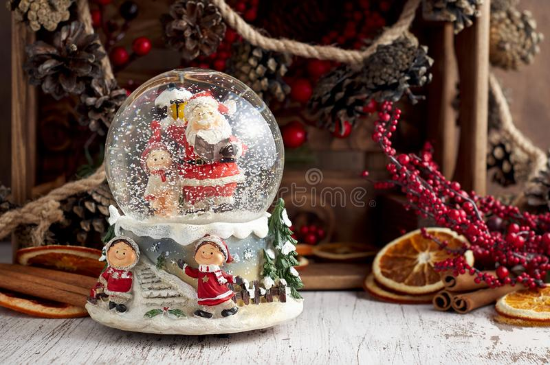 Musical Snow Globe with Santa Claus on wooden background. Musical Snow Globe with Santa Claus. Christmas or New Year gift on wooden background. Close up view stock images