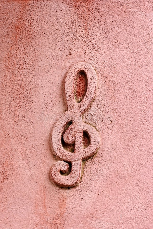 Musical symbol on wall stock photos