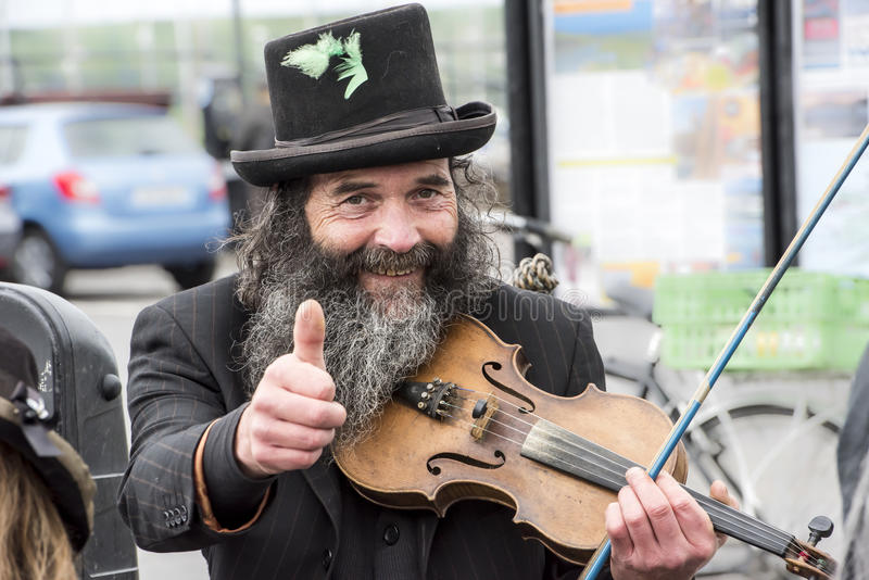 Musican and puppeteer, Ireland. Thumps up, street artist with fidel in Dingle, Ireland stock image