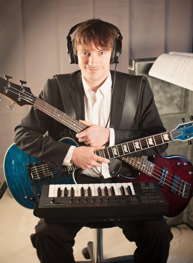 Musiciaanse portret in studio met twee gitaren en toetsenbord royalty-vrije stock fotografie