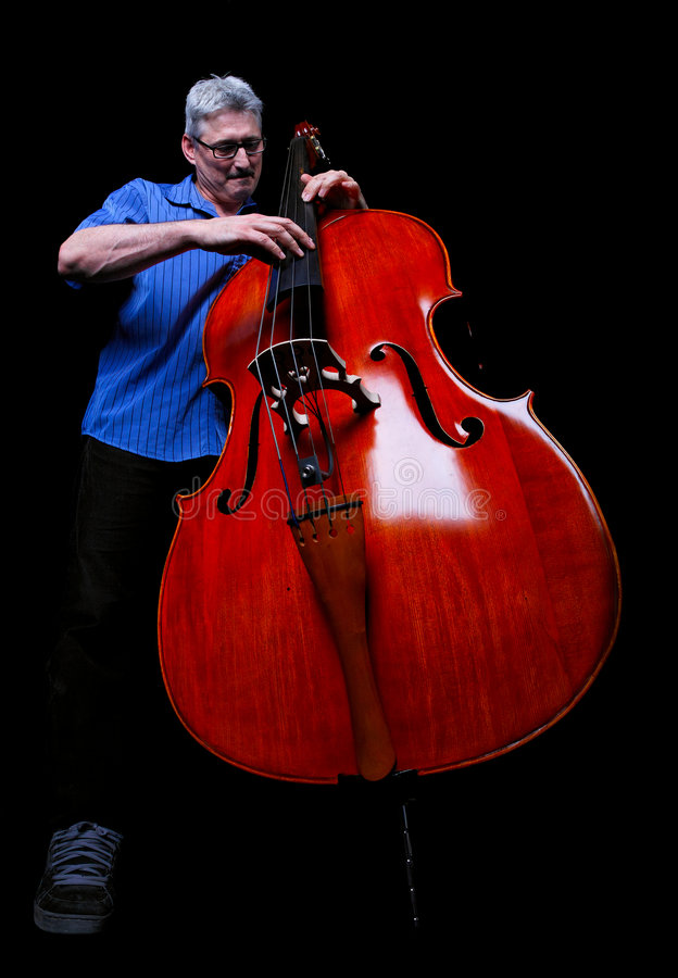 Musician. A musician playing a double bass low angle shot on a black background royalty free stock photo