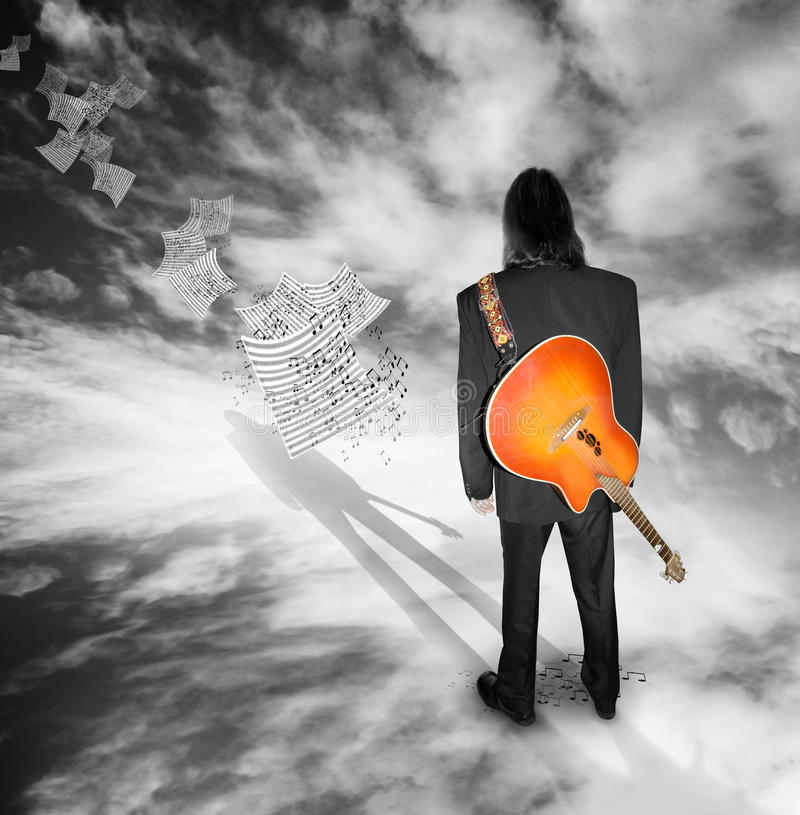 Musician. A suited musician with a guitar over his shoulder looks into the distance at fly away musical sheets with notes coming off the page royalty free stock images
