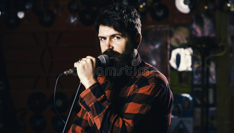 Musician with beard and mustache singing song in karaoke. Hipster likes to sing on stage. Music and leisure concept. Man royalty free stock images