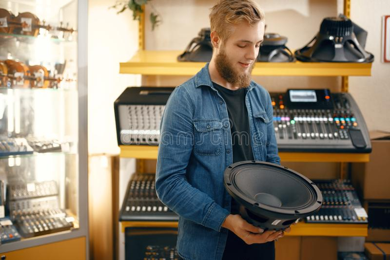 Musician buying subwoofer speaker in music store stock image