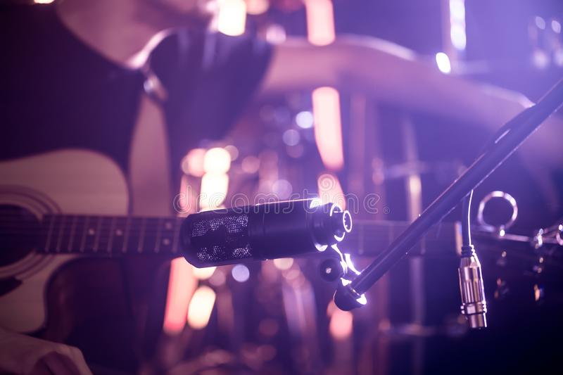The musician connects the microphone to record an acoustic guitar close-up, in a recording Studio or concert hall. The musician connects the microphone to royalty free stock photography