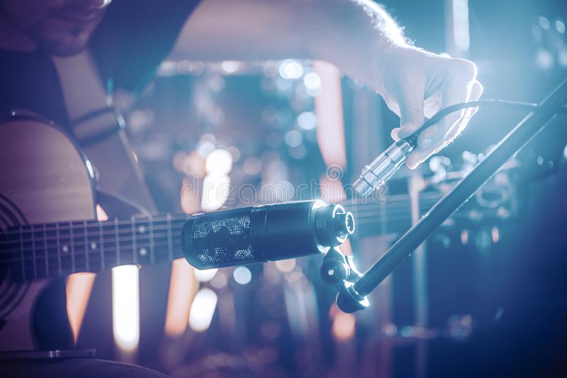 The musician connects the microphone to record an acoustic guitar close-up, in a recording Studio or concert hall. Beautiful blurred background of colored royalty free stock images