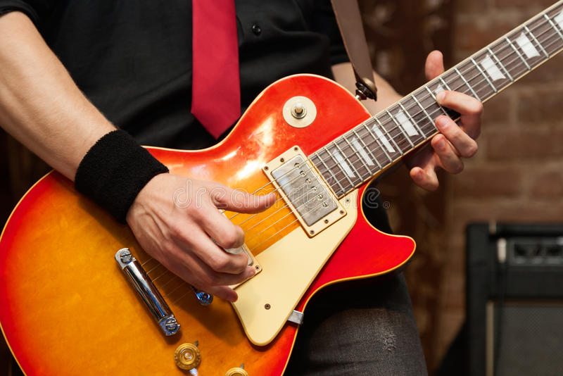 Musician With Electric Guitar. Musician performs solo on electric guitar. Close-up, shallow depth of field stock photo