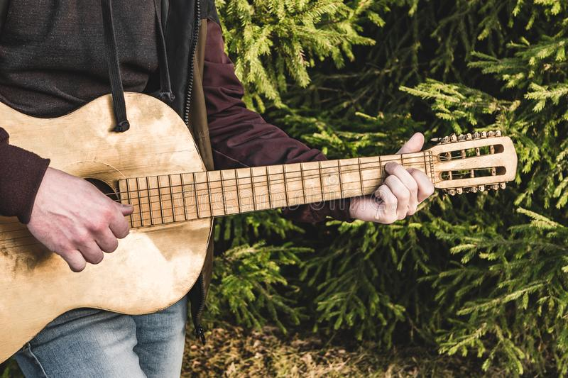 Musician with guitar on the grass royalty free stock images
