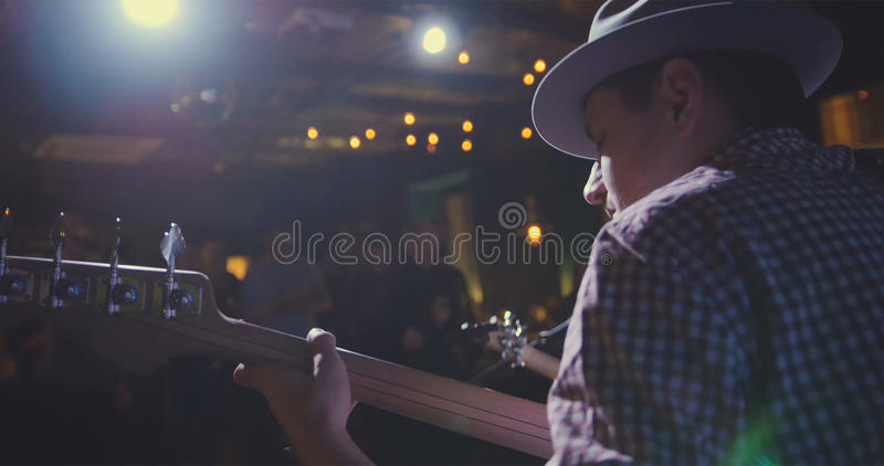 Musician - guitarist in hat plays guitar in night club, rear view. Close up stock photography