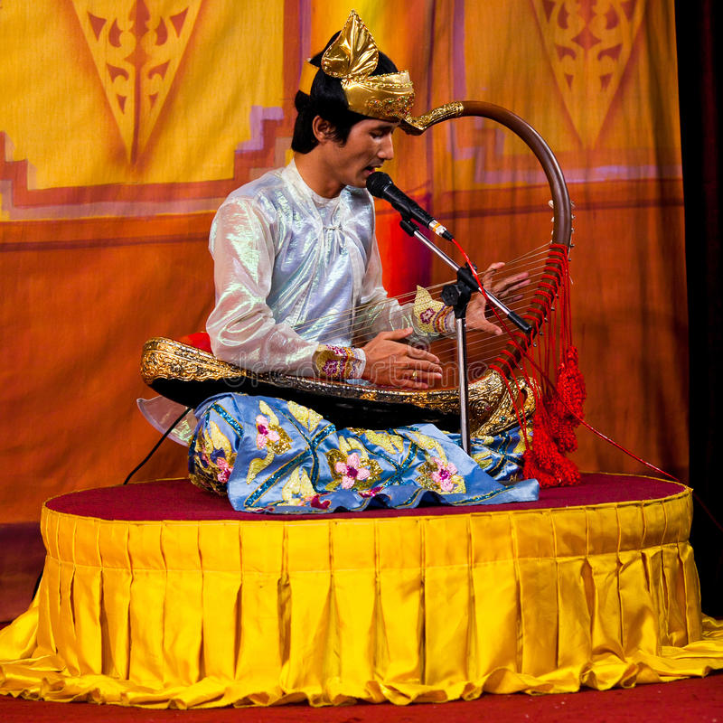 Musician with Harp, Myanmar. YANGON, MYANMAR - JANUARY 25: Musician with Harp plays on the evening show at Karaweik Hall on January 25, 2011 in Yangon, Myanmar stock photography