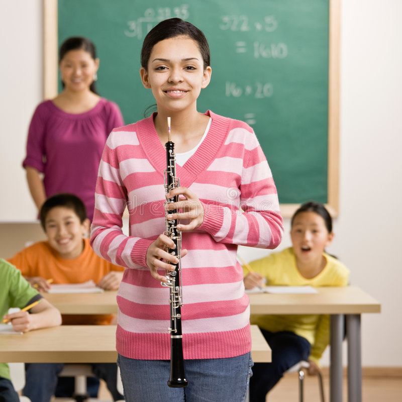 Musician holds clarinet in school classroom stock photo