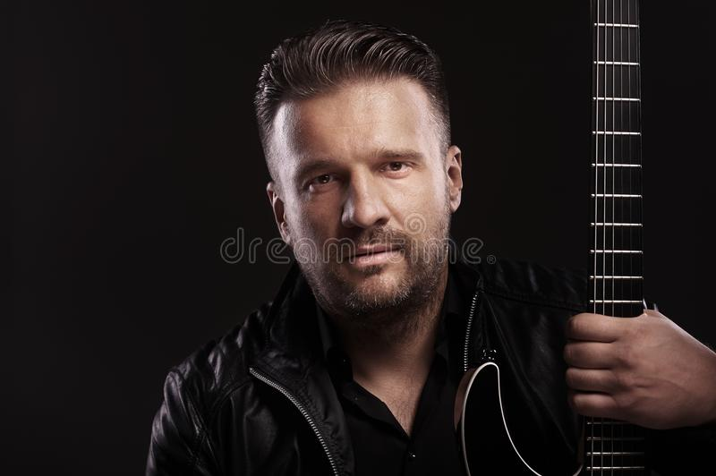 Musician male sits with guitar stock photography