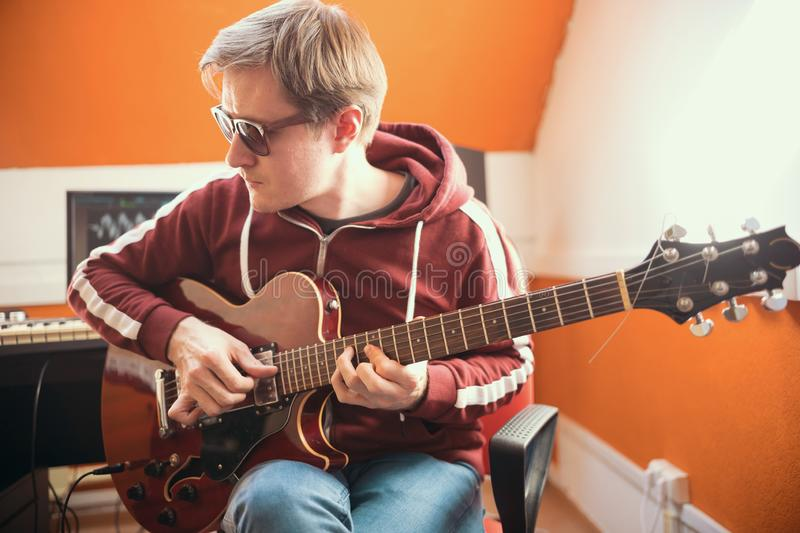 A musician man in glasses playing guitar and recording a song in the studio. Mid shot stock photo