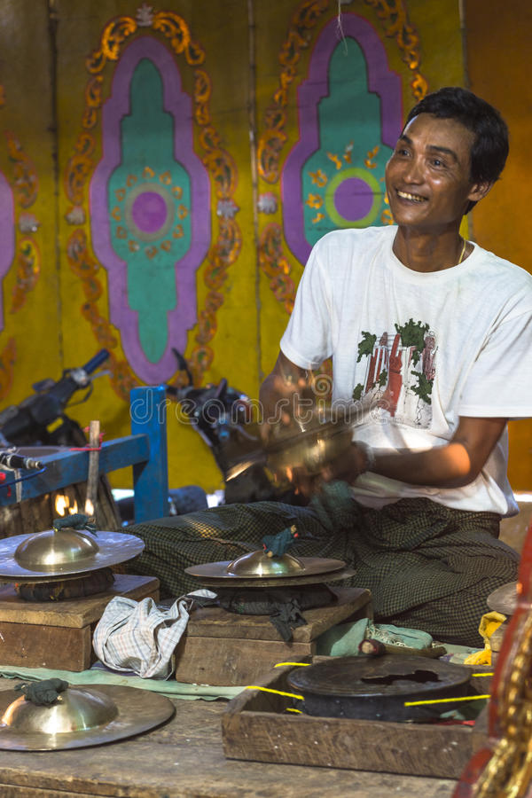 Musician. The man in time of playing music on a traditional music instrument during the holidays religious in a small village in Myanmar (Burma royalty free stock photo