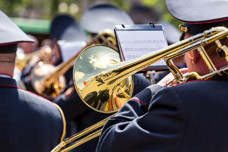 Musician of the military orchestra playing on gold trombone royalty free stock photo