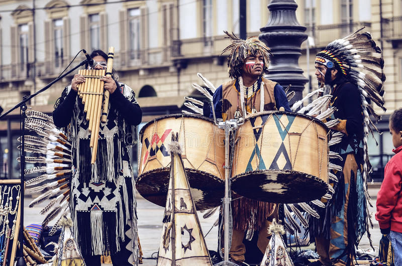 Musician Native Americans. Turin, Italy - April 27, 2013: Red indian in traditional costume plays in the center of Turin, Italy. Street performance of a group of stock images