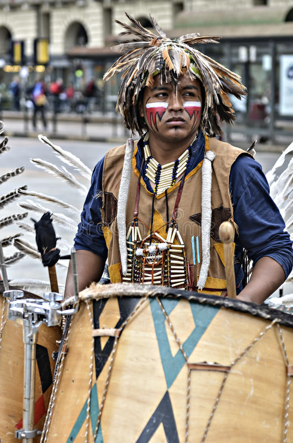 Musician Native Americans. Turin, Italy - April 27, 2013: Red indian in traditional costume plays in the center of Turin, Italy. Street performance of a group of royalty free stock photos